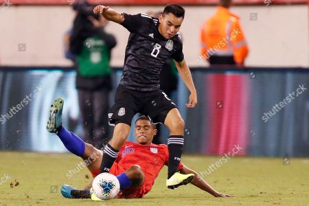 Mexico midfielder Carlos Rodriguez (8) steals the ball from United States defender Reggie Cannon (20) in the second half of an international friendly soccer match, in East Rutherford, N.J. Mexico defeated the U.S. 3-0