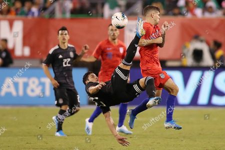 Stock Image of Mexico defender Jorge Sanchez, center, performs a bicycle kick to clear the ball while United States midfielder Christian Pulisic, right, protects himself during an international friendly soccer match, in East Rutherford, N.J. Mexico won 3-0