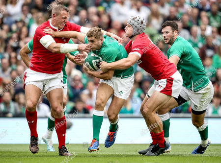 Ireland vs Wales. Ireland's Jordan Larmour tackled by Wales' Hadleigh Parkes and Jonathan Davies