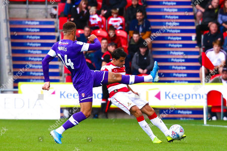 Carlton Morris of Rotherham United attempts to block a long ball by Reece James of Doncaster Rovers
