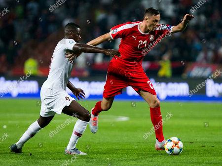 Milan Pavkov of Serbia competes against William Carvalho of Portugal