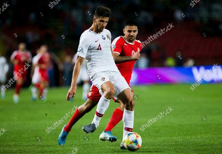 Ruben Dias of Portugal defends the ball from Aleksandar Mitrovic of Serbia