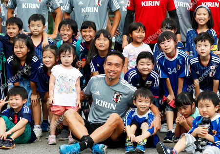 Japanese national soccer team player Yuto Nagatomo (C) poses for photographers with Japanese children during his team's training session in Yangon, Myanmar, 07 September 2019. Japan will face Myanmar in their FIFA World Cup 2022 qualifying group F soccer match on 10 September 2019.