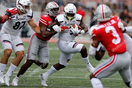 Cincinnati running back Michael Warren, center, tries to cut upfield past Ohio State linebacker Baron Browning during the first half of an NCAA college football game, in Columbus, Ohio