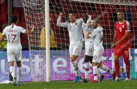 Portugal's William Carvalho (14) celebrates with teammates after scoring the opening goal during the Euro 2020 group B qualifying soccer match between Serbia and Portugal, on the stadium Rajko Mitic in Belgrade, Serbia