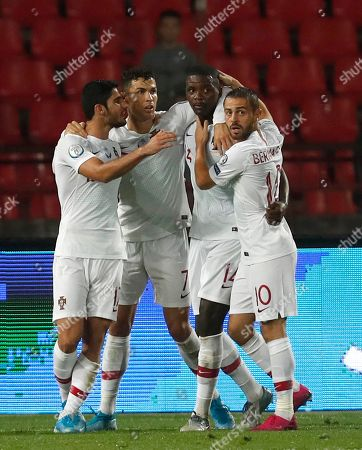 Portugal's William Carvalho, second right, celebrates with teammates after scoring the opening goal during the Euro 2020 group B qualifying soccer match between Serbia and Portugal, on the stadium Rajko Mitic in Belgrade, Serbia