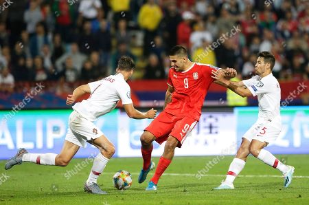 Serbia's Aleksandar Mitrovic (C) scores his team's second goal against Portuguese players Ruben Dias (L) and Raphael Guerreiro (R)  during the UEFA EURO 2020 group B qualifying soccer match between Serbia and Portugal in Belgrade, Serbia, 07 September 2019.