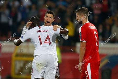 Portugal's Cristiano Ronaldo, center, and William Carvalho, left, jubilate after scoring a goal as Serbia's Matija Nastasic looks on during their Euro 2020 group B qualifying soccer match at the Rajko Mitic stadium in Belgrade, Serbia