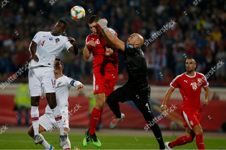 Portugal's William Carvalho, left, jumps for the ball against Serbia's Nikola Milenkovic, center, and Serbia's goalkeeper Marko Dmitrovic center right, during their Euro 2020 group B qualifying soccer match at the Rajko Mitic stadium in Belgrade, Serbia