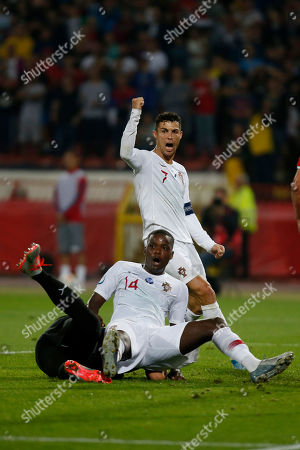 Portugal's Cristiano Ronaldo, back, jubilates after Portugal's William Carvalho, front, had scored a goal against Serbia during their Euro 2020 group B qualifying soccer match at the Rajko Mitic stadium in Belgrade, Serbia