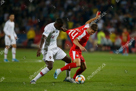 Serbia's Darko Lazovic, right, duels for the ball with Portugal's William Carvalho during their Euro 2020 group B qualifying soccer match at the Rajko Mitic stadium in Belgrade, Serbia