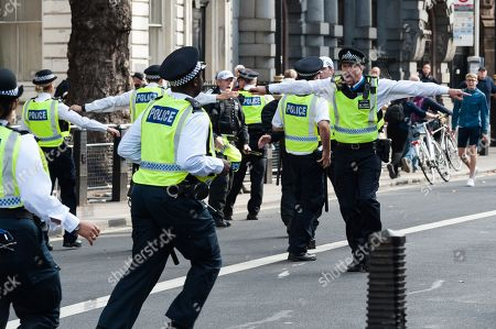 Police officers cordon off pro-Brexit supporters of Tommy Robinson and Boris Johnson in Whitehall as hundreds of pro-EU demonstrators take part in 'Stop the Coup' protests against the prorogation of the UK Parliament.