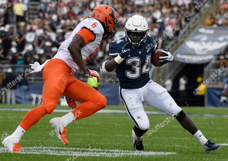 Connecticut running back Kevin Mensah (34) is pursued by Illinois defensive back Tony Adams (6) during the first half of an NCAA college football game, in East Hartford, Conn
