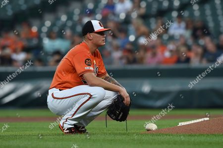Baltimore Orioles pitcher Aaron Brooks squats after his ball hit Texas Rangers Shin-Soo Choo and home plate umpire Jim Reynolds on a pitch in the first inning of a baseball game, in Baltimore