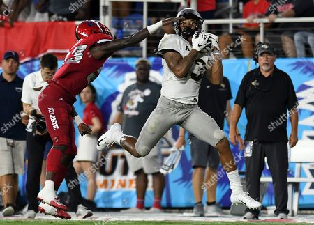 UCF wide receiver Gabriel Davis hauls in a pass for a big gain as Florida Atlantic cornerback James Pierre (23) defends during the first half of an NCAA college football game, in Boca Raton, Fla