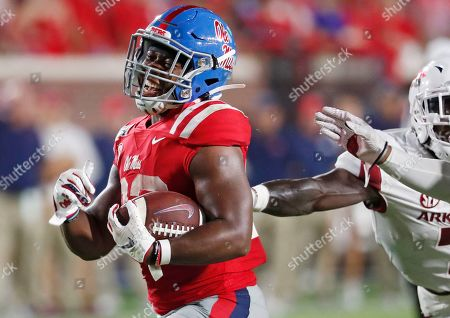 Mississippi running back Scottie Phillips (22) laughs as he runs past Arkansas defenders on his way to a touchdown during the second half of an NCAA college football game, in Oxford, Miss. Mississippi won 31-17