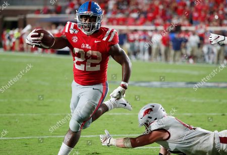 Mississippi running back Scottie Phillips (22) holds out his arm as he scores on a one-yard touchdown run past a fallen Arkansas defender during the second half of their NCAA college football game, in Oxford, Miss. Mississippi won 31-17