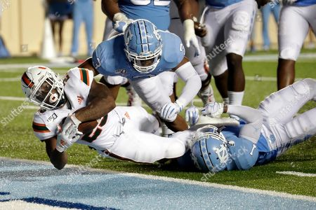 Miami's Cam'Ron Harris (23) gets past North Carolina's Dominique Ross (3) and Myles Dorn (1) to score a touchdown during the third quarter of an NCAA college football game in Chapel Hill, N.C