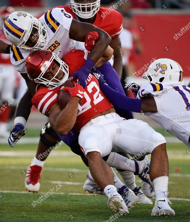 Stock Photo of Houston running back Kyle Porter, bottom, is tackled by Prairie View defensive end Isaiah Washington, left, and defensive back Darius Campbell during the first half of an NCAA college football game, in Houston