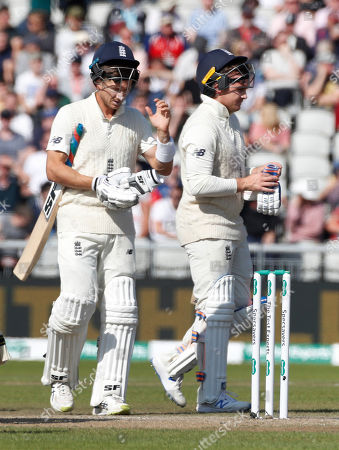 England's Joe Denly, left, and England's Jason Roy after drinks break during day five of the fourth Ashes Test cricket match between England and Australia at Old Trafford in Manchester, England