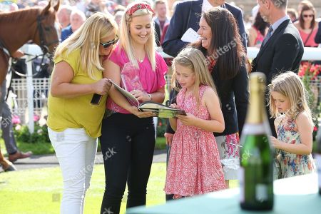 The Macmillan Riders families looking through the books that were presented to the Macmillan Riders during the Family Race Day held at York Racecourse, York