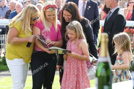 Stock Photo of The Macmillan Riders families looking through the books that were presented to the Macmillan Riders during the Family Race Day held at York Racecourse, York