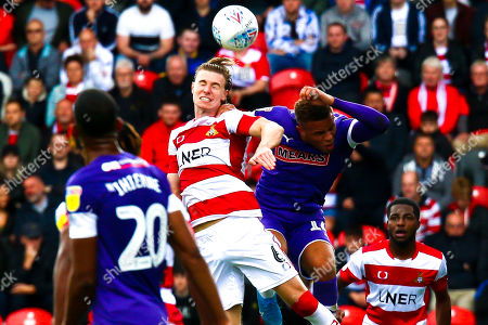 Ben Sheaf of Doncaster Rovers beats Carlton Morris of Rotherham United to head the ball