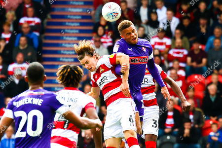 Carlton Morris of Rotherham United and Ben Sheaf of Doncaster Rovers jump to head the ball