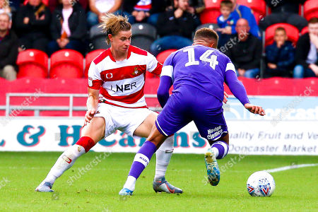 Ben Sheaf of Doncaster Rovers attempts to stop an attack by Carlton Morris of Rotherham United
