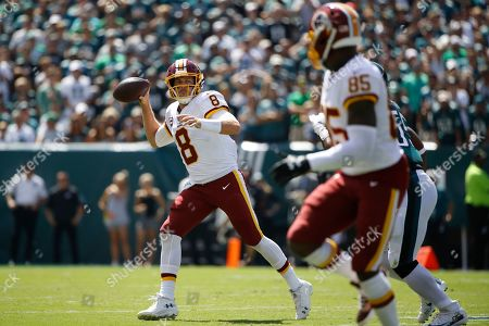 Washington Redskins' Case Keenum, left, throws a touchdown pass to Vernon Davis during the first half of an NFL football game against the Philadelphia Eagles, in Philadelphia