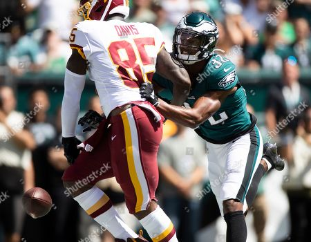 Philadelphia Eagles cornerback Rasul Douglas, right, punches the ball out of the hands of Washington Redskins tight end Vernon Davis after Davis scored a touchdown during an NFL football game, in Philadelphia, PA
