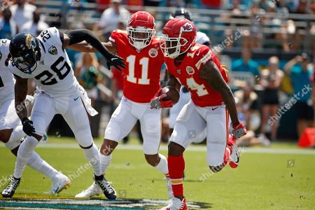 Kansas City Chiefs wide receiver Sammy Watkins, right, runs for a 68-yard touchdown on a pass play as he gets a block from wide receiver Demarcus Robinson (11) on Jacksonville Jaguars defensive back Jarrod Wilson (26) during the first half of an NFL football game, in Jacksonville, Fla