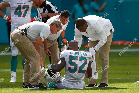 Miami Dolphins middle linebacker Raekwon McMillan (52) is attended on the field, during the second half at an NFL football game against the Baltimore Ravens, in Miami Gardens, Fla