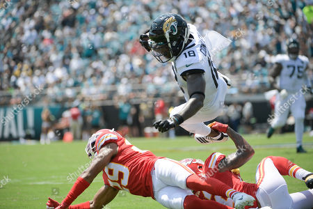 Jacksonville Jaguars wide receiver Chris Conley (18) dives over Kansas City Chiefs cornerback Kendall Fuller, lower left, after a reception during the first half of an NFL football game, in Jacksonville, Fla