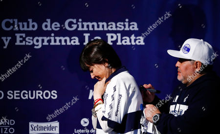 Former soccer great Diego Maradona signs the jersey of Giselle Fernandez, the sister of former Argentine President Cristina Fernandez de Kirchner, during a news conference after Maradona's presentation as the new head coach of Gimnasia y Esgrima La Plata in La Plata, Argentina