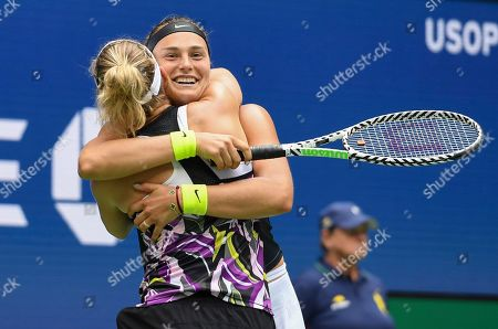 Arena Sabalenka, of Belarus, right, celebrates with doubles partner Elise Mertens, of Belgium, after winning the women's doubles final against Victoria Azarenka, of Belarus, and Ashleigh Barty, of Australia, at the U.S. Open tennis championships, in New York