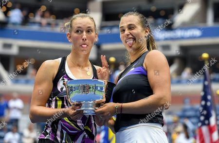 Elise Mertens, of Belgium, left, poses for photos with the trophy with doubles partner Arena Sabalenka, of Belarus, after winning the women's doubles final against Victoria Azarenka, of Belarus, and Ashleigh Barty, of Australia, at the U.S. Open tennis championships, in New York