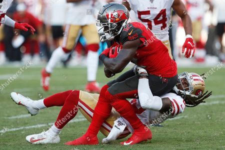 San Francisco 49ers cornerback Richard Sherman (25) tackles Tampa Bay Buccaneers wide receiver Chris Godwin (12) during the second half an NFL football game, in Tampa, Fla