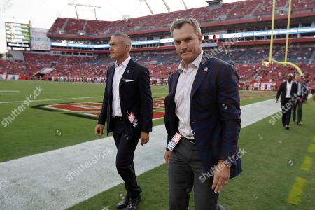 San Francisco 49ers General Manager John Lynch, right, walks the field during the second half an NFL football game, in Tampa, Fla. The San Francisco 49ers won 31-17