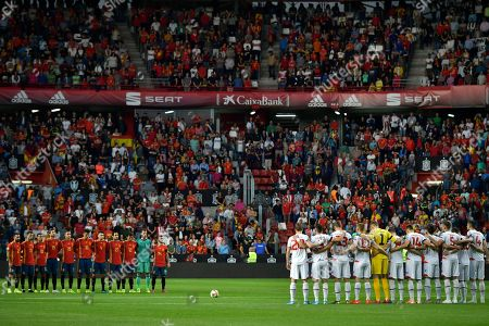 Spain team players, left and Faroe Island players stand during a minute of silence for former coach Luis Enrique's daughter Xana who died recently before the Euro 2020 group F qualifying soccer match between Spain and Faroe Islands at the Molinon, stadium in Gijon, Spain