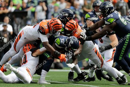 Seattle Seahawks running back Chris Carson (32) is tackled by Cincinnati Bengals' Carlos Dunlap (96) and Geno Atkins (97) during the first half of an NFL football game, in Seattle