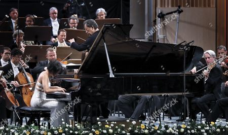 Stock Picture of Chinese classical pianist Yuja Wang (L), accompanied by The Staatskapelle Dresden orchestra under the batton of South Korean conductor Myung-whun Chung (C), performs Rachmaninoff's Piano Concerto no. 3 in D minor op. 30 the stage of Grand Concert Hall during the George Enescu International Festival 2019, in Bucharest, Romania, 08 September 2019. The festival, held since 1958 every two years, is the biggest classical music festival held in Romania, in honor of Romanian composer and violinist George Enescu. The 24th edition of the George Enescu International Festival takes place between 31 August and 22 September 2019.