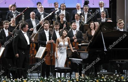 Stock Image of Chinese classical pianist Yuja Wang, backed by the musicians of The Staatskapelle Dresden orchestra, greets the audience after performing Rachmaninoff's Piano Concerto no. 3 in D minor op. 30 the stage of Grand Concert Hall during the George Enescu International Festival 2019, in Bucharest, Romania, 08 September 2019. The festival, held since 1958 every two years, is the biggest classical music festival held in Romania, in honor of Romanian composer and violinist George Enescu. The 24th edition of the George Enescu International Festival takes place between 31 August and 22 September 2019.