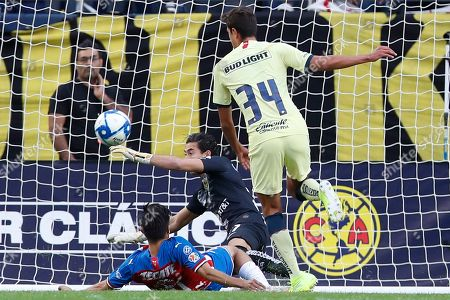 Stock Photo of Club America's Oscar Jimenez, center, knocks the ball away from Chivas de Guadalajara's Oribe Peralta as Club America's Haret Ortega looks on during the first half of the Super Clasico soccer match, in Chicago