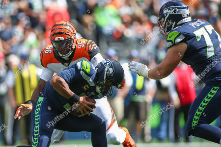Seattle Seahawks quarterback Russell Wilson (3) is sacked by Cincinnati Bengals defensive end Carlos Dunlap (96) during a game between the Cincinnati Bengals and Seattle Seahawks at CenturyLink Field in Seattle, WA. The Seahawks won 21-20