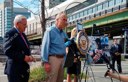 U.S. Sen. Charles Schumer, center, with New Jersey Sen. Bob Menendez, left, speaks before the media in New York on . Schumer is blasting a helicopter tour company involved in last year's fatal East River crash for operating doors-off helicopter flights for tourists and their dogs