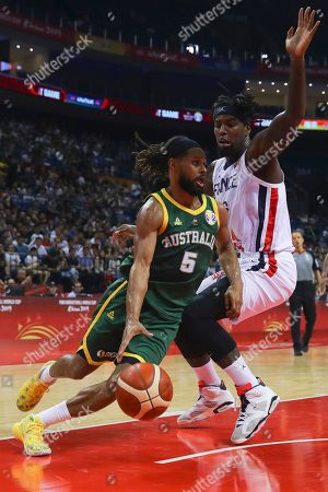 Matias Lessort (R) of France in action against Patty Mills (L) of Australia during the FIBA Basketball World Cup 2019 classification round group L match between France and Australia in Nanjing, China, 09 September 2019.