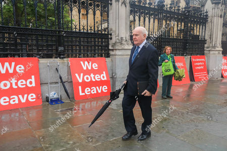 Stock Picture of Former Labour Home Secretary John Reid, Baron Reid of Cardowan ewalks past Vote leave placards in Westminster