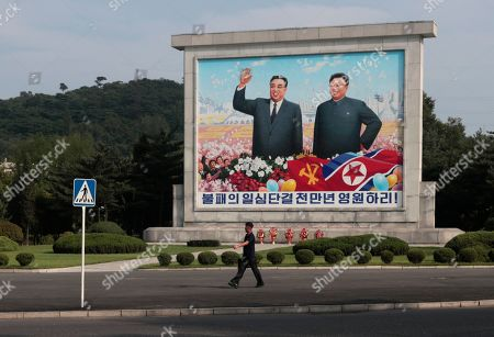 A man walks past a large mural of late North Korean leaders Kim Il Sung, and his son Kim Jong Il in Pyongyang, North Korea