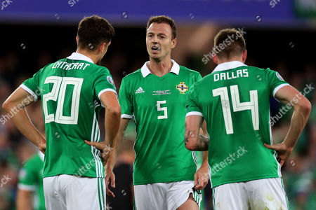 Jonny Evans of Northern Ireland speaks with Craig Cathcart and Stuart Dallas during a break in play